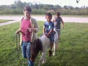 Comanche the mini horse graciously giving a quick ride.