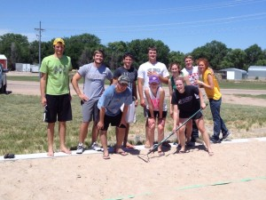 Alumni, out-of-state and out-of-country guest pose for a picture after a friendly sand volleyball game.