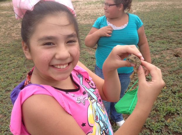 A Clovis Arts Academy 4th- grader poses with Woodhouse's toad that she found at Goodwin Playa
