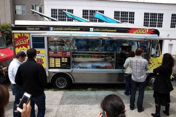 """SAN FRANCISCO, CA - JULY 07: Customers line up to order food from the Hiyaaa! food truck during an Off the Grid """"market"""" on July 7, 2014 in San Francisco, California. Popular San Francisco Bay Area food trucks are gathering at venues organzined by planning companies such Off the Grid that creates """"markets"""" for food trucks for a nominal fee that is far less than fines that are often handed out to food trucks that operate on city streets without proper permits. (Photo by Justin Sullivan/Getty Images)"""