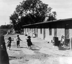 Hispanic children play near a house at a migrant workers' camp near Manzanola (Otero County), Colorado. A manual washing machine, lumber, and large metal drum are nearby. estern History/Genealogy Dept., Denver Public Library